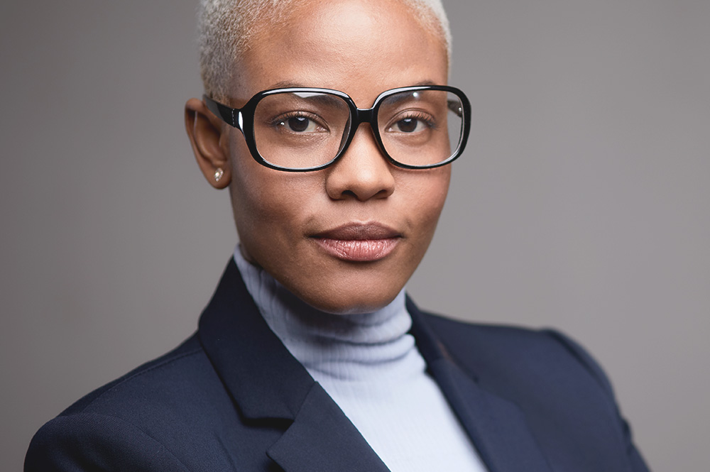 Picture of a woman wearing glasses for the product line of Constitution lenses from FEA Industries.
